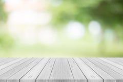 Leere weiße hölzerne Tischplatte auf Naturgrün verwischte Hintergrund Lizenzfreie Stockfotos