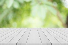 Leere weiße hölzerne Tischplatte auf Naturgrün verwischte Hintergrund Stockfotos