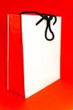 Leere weiße Papiertüte auf dem Rot Stockfotos