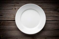 Leere weiße Platte auf hölzerner Tabelle Stockbild