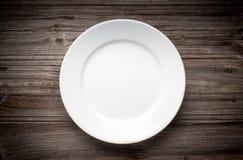 Leere weiße Platte auf hölzerner Tabelle Stockfotografie