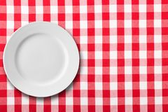 Leere weiße Platte auf roter karierter Tischdecke lizenzfreies stockfoto