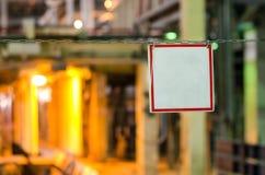 Leere weiße unterzeichnen herein den roten Rahmen, der an den Ketten hängt Stockbild