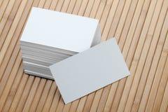 Leere weiße Visitenkarte auf hölzernem Hintergrund Lizenzfreie Stockbilder