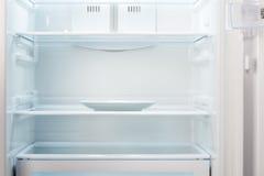 Leere weiße Platte im offenen leeren Kühlschrank Lizenzfreie Stockfotos