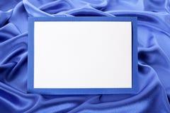 Leere Weihnachts- oder Geburtstagsgrußkarte oder -einladung mit blauem Satinhintergrund, Kopienraum stockbild