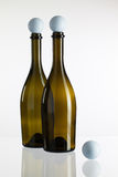 Leere Weinflaschen und -Golfbälle auf einem Glasschreibtisch Lizenzfreies Stockbild