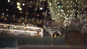 Leere Weinglasstellung auf einer Tabelle in einem Restaurant nahe bei einer Blume in einem Topf Abschluss oben stock video footage