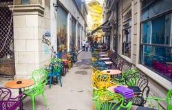 Leere Weinleseterrasse im historischen Stadtzentrum mit mehrfarbigen Stühlen auf dem Pflasterungsbürgersteig Bunte Stühle in Retr lizenzfreies stockbild