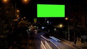 Leere Werbungsanschlagtafel neben Straße mit Verkehr nachts stock video