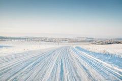 Leere Winterstraße bedeckt mit Schnee auf Feld in der Bewegung Stockfotografie
