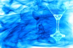 Leeren Sie das Cocktailglas, das im blauen Rauche eingeschlagen wird Stockfoto