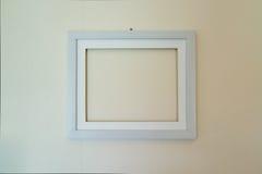 Leeren Sie den hölzernen Bilderrahmen, der an der Wand angebracht wird Lizenzfreie Stockfotos