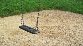 Leeren Sie den Schwingensitz, der am Spielplatz im Park beeinflußt Stockfotos