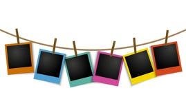 Leeren Sie die bunten Fotorahmen, die am Seil mit Stift hängen Stockfotos