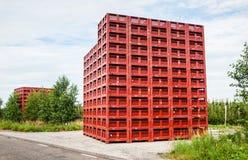 Leeren Sie die roten Sammelnkisten, die nahe einem Obstgarten gestapelt werden Lizenzfreies Stockbild