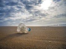 Leeren Sie die zerknitterte Plastikflasche Wasser verlassen auf dem Strand bei Sonnenuntergang lizenzfreie stockbilder