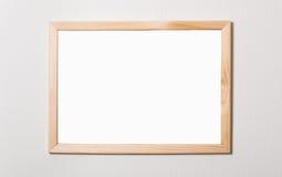Leeren Sie einen Holzrahmen auf einer weißen Wand Lizenzfreies Stockbild