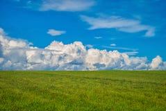 Leeren Sie Feld mit grünem Gras und Wolken Lizenzfreie Stockfotografie
