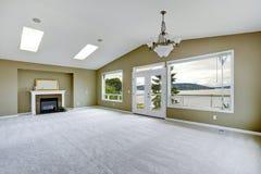 Leeren Sie geräumiges Wohnzimmer mit Arbeitsniederlegungsplattform und -kamin Stockbild