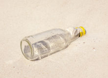 Leeren Sie Glasflasche auf nahe gelegener Küstenlinie des Strandsandes Lizenzfreies Stockbild