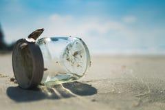 Leeren Sie Glasflasche auf sandigem Strand mit blauem Himmel und Meer Lizenzfreie Stockfotos