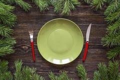 Leeren Sie grüne Platte mit Messer- und Gabel- und Kiefernniederlassungen auf woode Stockfotografie