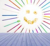 Leeren Sie hölzerne Plattformtabelle mit der lächelnden Sonne, die von den Zeichenstiften vereinbart wird und auf blauem Hintergr Stockfotografie