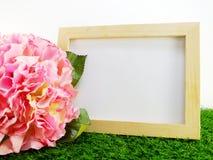 Leeren Sie Holzrahmen mit Blume auf grünem Hintergrund Lizenzfreie Stockbilder