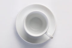 Leeren Sie klare Kaffeetasse auf Untertasse gegen weißen Hintergrund, Draufsicht Lizenzfreie Stockbilder