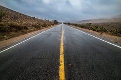 Leeren Sie nasse Wüstenasphalt-Pflasterungsstraße mit gelben Landstraßenmarkierungslinien Stockfoto
