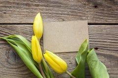 Leeren Sie Papierkarte mit gelben Tulpen auf altem hölzernem Hintergrund pl Lizenzfreie Stockbilder