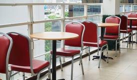 Leeren Sie rote Stühle und runde Holztische im hohen Gebäude stockbilder