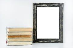 Leeren Sie schwarzen Rahmen und Stapel alte Bücher auf weißem Hintergrund Stockfoto