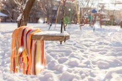 Leeren Sie Schwingen mit Schnee und kariertem Schal Stockfotos