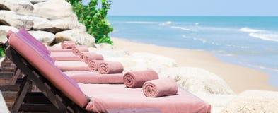 Leeren Sie sich sunbed mit eingewickelten Tüchern auf einem schönen Strand Stockfotografie