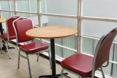 Leeren Sie sich von den roten Stühlen und von den runden Holztischen am Morgen lizenzfreie stockbilder