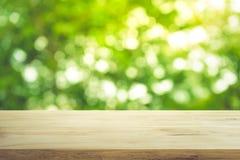Leeren Sie sich von der hölzernen Tischplatte auf Unschärfe des frischen grünen abstrakten Gartens Lizenzfreie Stockfotografie