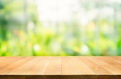Leeren Sie sich von der hölzernen Tischplatte auf Unschärfe von neuen grünen Hintergründen Lizenzfreie Stockbilder