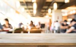 Leeren Sie sich von der hölzernen Tischplatte, die an von den Leuten in der Kaffeestube verwischt wird Stockfotografie