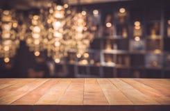 Leeren Sie sich von der hölzernen Tischplatte mit unscharfem hellem Gold-bokeh Zusammenfassungshintergrund Lizenzfreie Stockbilder