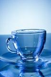 Leeren Sie transparenten Glasbecher auf blauem Hintergrund Stockfotos