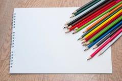 Leeren Sie Weißbuch und bunte Bleistifte auf dem hölzernen Stockfotos