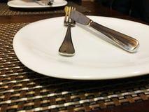 Leeren Sie weiße Platte auf brauner Tabelle mit Messer und Gabel Lizenzfreie Stockbilder