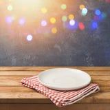 Leeren Sie weiße Platte auf Holztisch über Tafelhintergrund mit bokeh Lichtern Geburtstags- oder Feiertagsfeier Stockbild