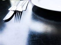 Leeren Sie weiße Platte auf schwarzer Tabelle mit Messer und Gabel Lizenzfreie Stockfotografie