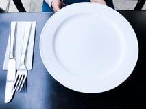 Leeren Sie weiße Platte auf schwarzer Tabelle mit Messer und Gabel Lizenzfreie Stockfotos