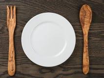 Leeren Sie weiße Platte mit hölzerner Gabel und Löffel auf eichenem Tisch Stockfotografie
