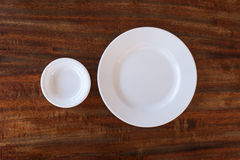 Leeren Sie weiße Platte und kleinen Messkelch auf hölzernem Hintergrund lizenzfreie stockbilder