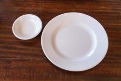 Leeren Sie weiße Platte und kleinen Messkelch auf Holztisch Stockbild